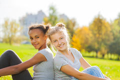 Afrikanisches und blondes Mädchen, das zusammen im Park sitzt Lizenzfreies Stockfoto