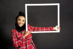 Afrikanisches weibliches vorbildliches Holding ein Rahmen stockfotos