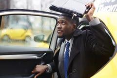 Afrikansk affärsman Leaving Taxi i regn royaltyfria bilder