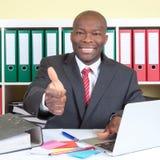 Afrikansk affärsmanvisningtumme upp på hans kontor Arkivbild