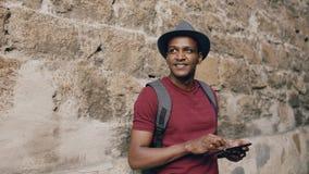 Afrikansk amerikan som ler den turist- mannen som använder minnestavlaonline-översikten för att finna rätta riktningar som står p Royaltyfri Foto