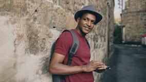 Afrikansk amerikan som ler den turist- mannen som använder minnestavlaonline-översikten för att finna rätta riktningar som står p Arkivfoto