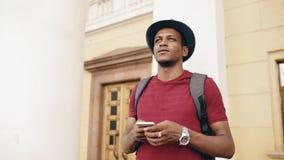Afrikansk amerikan som ler den turist- mannen som använder smartphoneonline-översikten för att finna rätta riktningar som står på Arkivbild
