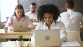Afrikansk amerikanaffärskvinna som arbetar på bärbara datorn med grafer, i coworking