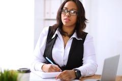 Afrikansk amerikanaffärskvinnan är upptagen med pappers- jobb i regeringsställning royaltyfri foto