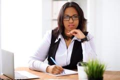 Afrikansk amerikanaffärskvinnan är upptagen med pappers- jobb i regeringsställning arkivbild
