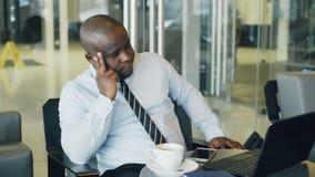 Afrikansk amerikanaffärsman i formella kläder som ser hans bärbar dator och tänker över hans affärsplan i stilfullt kafé stock video