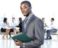 Afrikansk amerikanaffärsman i modernt kontor med kollegor Arkivfoton