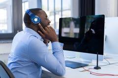 Afrikansk amerikanaffärsman Listen To Music med hörlurar i modernt Coworking utrymme, vuxen affärsman som kopplar av på royaltyfria foton