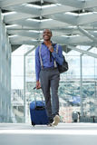 Afrikansk amerikanaffärsman som går på flygplatsen med bagage royaltyfri foto