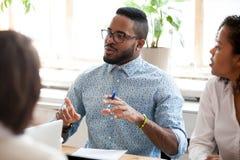 Afrikansk amerikanaffärsman som talar om idéer på förhandsmöte arkivfoton