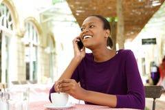 Afrikansk amerikandam på coffee shop genom att använda mobiltelefonen Arkivbilder