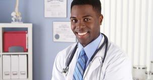 Afrikansk amerikandoktor som i regeringsställning ler royaltyfri foto
