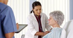 Afrikansk amerikandoktor som lyssnar till äldre patients hjärta med stetoskopet royaltyfri fotografi