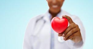 Afrikansk amerikandoktorshand som rymmer röd hjärta arkivbild