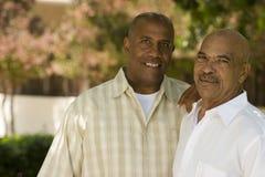 Afrikansk amerikanfader och hans vuxna son Fotografering för Bildbyråer