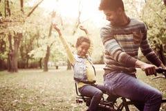 Afrikansk amerikanfader som kör hans liten flicka på cykeln tr royaltyfri bild
