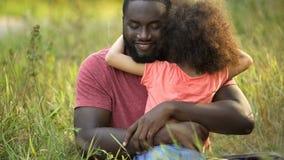 Afrikansk amerikanfader som tycker om nöjetidsfördriv med hans lilla dotter arkivfoto