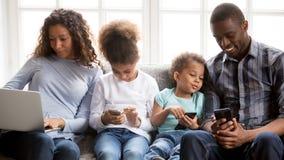 Afrikansk amerikanfamilj att koppla av hemma genom att använda grejer arkivfoto