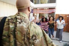 Afrikansk amerikanfamilj för tre utveckling som välkomnar soldaten som hem går tillbaka, över skuldrasikt arkivbilder