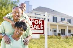 Afrikansk amerikanfamilj framme av det Sale tecknet och huset Royaltyfri Foto