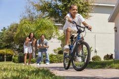 Afrikansk amerikanfamilj med pojkeridningcykeln & lyckliga föräldrar arkivfoto