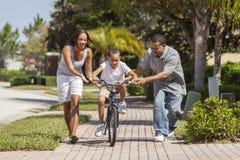 Afrikansk amerikanfamilj med pojkeridningcykeln & lyckliga föräldrar arkivfoton
