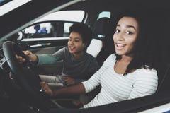 Afrikansk amerikanfamilj på bilåterförsäljaren Modern och sonen sitter i ny bil arkivfoton