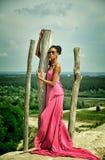 Afrikansk amerikanflicka i en rosa klänning på en kulle mot himlen Arkivbild