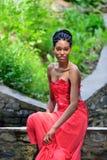 Afrikansk amerikanflicka med dreadlocks som sitter på stenarna i parkera, poserar, ler och ser in i kameran Royaltyfri Fotografi