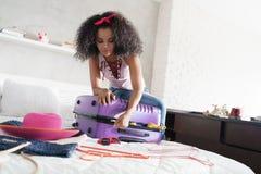Afrikansk amerikanflicka som förbereder bagage för semester och lopp arkivbilder