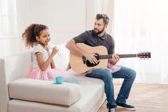 Afrikansk amerikanflicka som sjunger medan fader som hemma spelar gitarren Arkivfoto