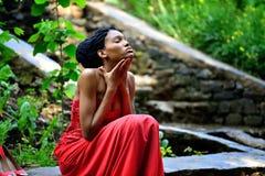 Afrikansk amerikanflickan i en röd klänning, med dreadlocks som sitter i sommaren på en bakgrund av gröna växter på, vaggar Royaltyfri Foto