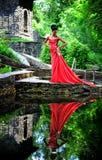 Afrikansk amerikanflickan i en röd klänning med röda skor i hand är värd i sommaren på vattnet på stenarna i parkera Arkivbilder