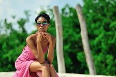 Afrikansk amerikanflickan med dreadlocks, bärande solglasögon, rosa färger klär, sitter och drömmer överst av en kulle på en soli Royaltyfri Fotografi