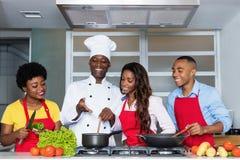 Afrikansk amerikanfolket lär matlagning från kock arkivbild
