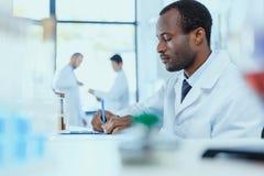 Afrikansk amerikanforskare i det vita laget som tar anmärkningar, medan arbeta i laboratorium Royaltyfri Fotografi