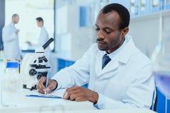 Afrikansk amerikanforskare i det vita laget som tar anmärkningar, medan arbeta i laboratorium Arkivfoto