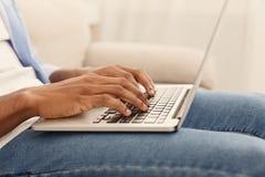 Afrikansk amerikangrabb som spelar videospelet på bärbara datorn arkivbild