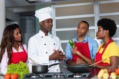 Afrikansk amerikankock med kvinnor och mannen på kök royaltyfri bild