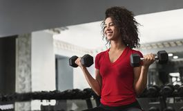 Afrikansk amerikankonditionkvinna som gör bicepsgenomkörare i idrottshall arkivfoton