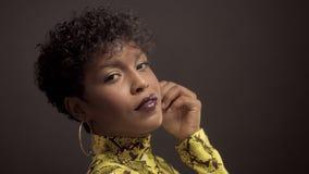 Afrikansk amerikankvinna för blandat lopp i ljus gul klänning med pytonormtrycket stil för 90 ` s stock video