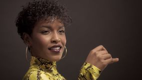 Afrikansk amerikankvinna för blandat lopp i ljus gul klänning med pytonormtrycket stil för 90 ` s lager videofilmer