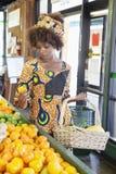 Afrikansk amerikankvinna i traditionell klädershopping för frukter på supermarket Royaltyfria Bilder