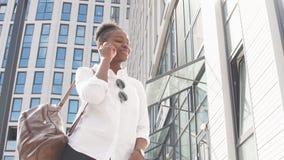Afrikansk amerikankvinna med att gå för ryggsäck som är utomhus-, och samtal på mobiltelefonen lager videofilmer