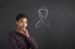 Afrikansk amerikankvinna med handen på hakan som tänker om sjukdommedvetenhet på svart tavlabakgrund Arkivfoto