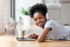 Afrikansk amerikankvinna som använder en bärbar dator i hennes vardagsrum - svart Royaltyfri Foto