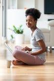 Afrikansk amerikankvinna som använder en bärbar dator i hennes vardagsrum - svart Arkivbilder