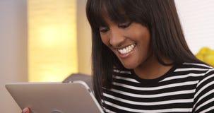 Afrikansk amerikankvinna som använder minnestavlan i vardagsrum arkivbild