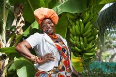 Afrikansk amerikankvinna som bär en ljus färgrik nationell klänning fotografering för bildbyråer